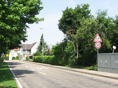 Ortseinfahrt aus Richtung Weitenung: Ein Schild und eine Markierung auf der Fahrbahn weisen auf die Geschwindigkeitsbegrenzung hin.